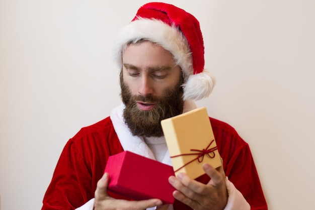 Serious guy wearing santa costume and looking into gift box Free Photo