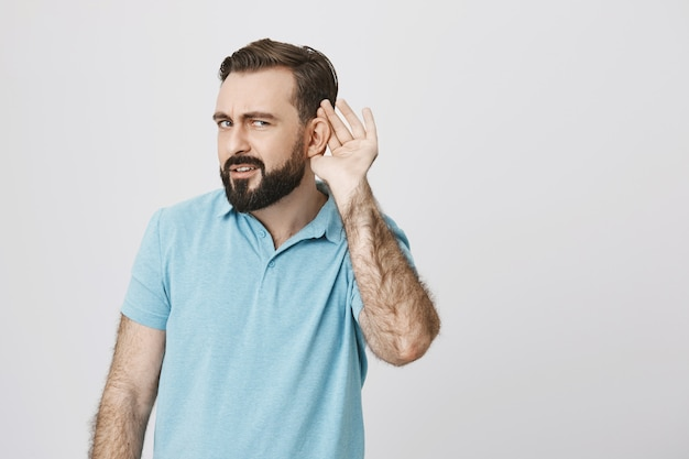 Serious handsome bearded guy eavesdropping, trying listen Free Photo