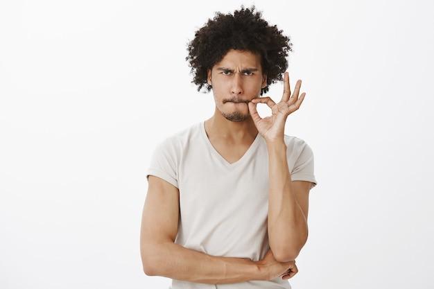 Un bell'uomo serio promette di non parlare, chiudendo la bocca sul sigillo Foto Gratuite