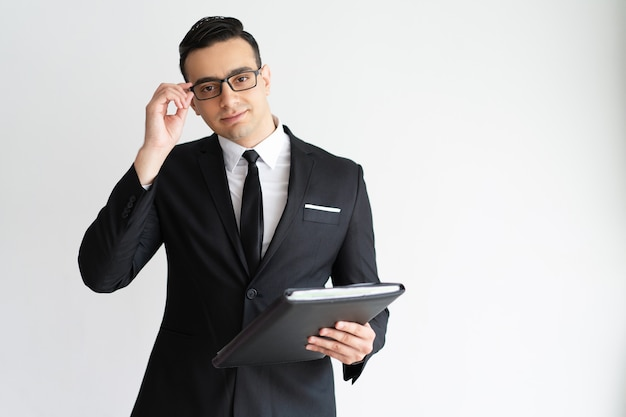 Serious handsome young businessman adjusting glasses and holding folder. Free Photo