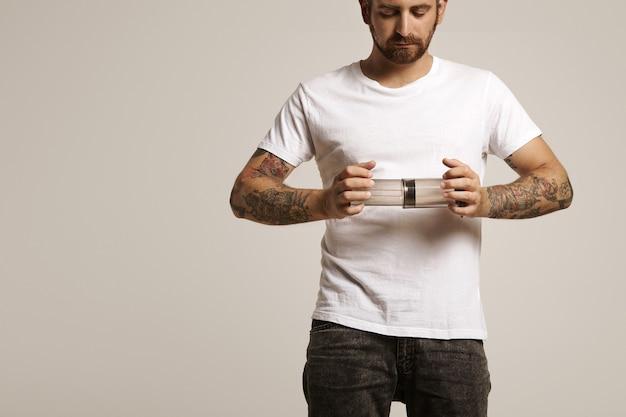 Серьезный красивый молодой человек в белой футболке без надписи и джинсах, держащий пустой аэропресс Бесплатные Фотографии