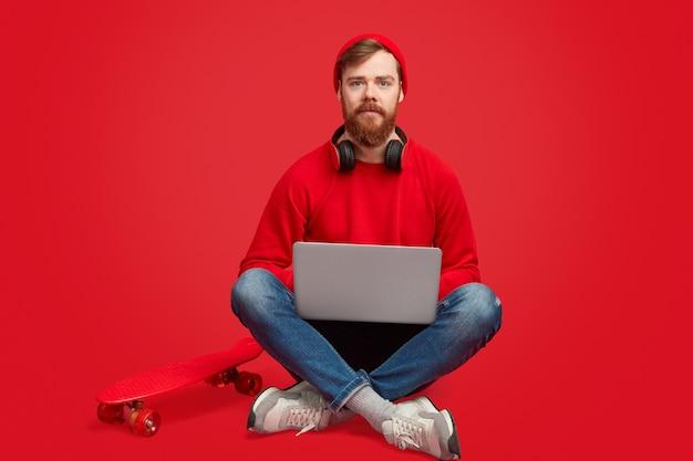 ノートパソコンとスケートボードを持つ深刻な流行に敏感な男 Premium写真