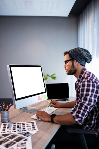 Serious hipster working at computer desk Premium Photo