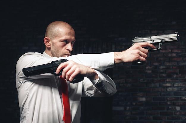 赤いネクタイで真剣に雇われた暗殺者は2つのピストルで狙いを定めます Premium写真