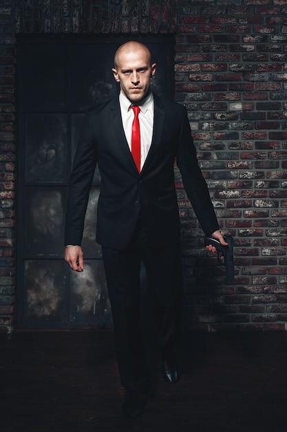 銃を持った赤で真剣に雇われた殺人者 Premium写真