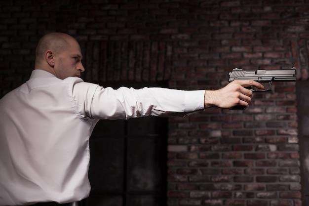 赤いネクタイで真面目な雇われた殺人者が銃を狙う Premium写真