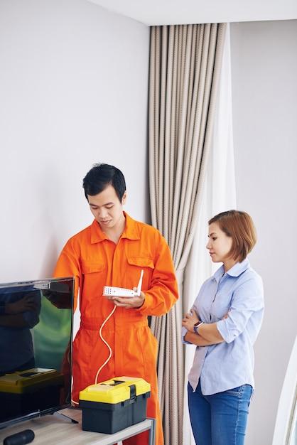 Серьезная домохозяйка, контролирующая техник, устанавливает wi-fi роутер в своей комнате Premium Фотографии