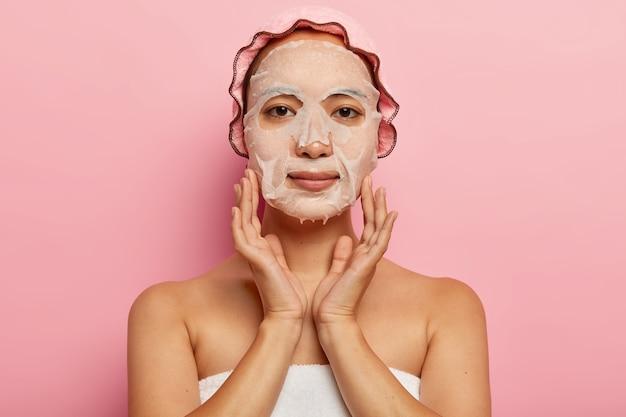 진지한 일본 여성은 얼굴에 영양 마스크를 쓰고 피부에 보습 시트 제품을 바르고 목욕 모자를 쓰고 분홍색 벽에 포즈를 취합니다. 여성, 미용 및 스파 트리트먼트 개념 무료 사진