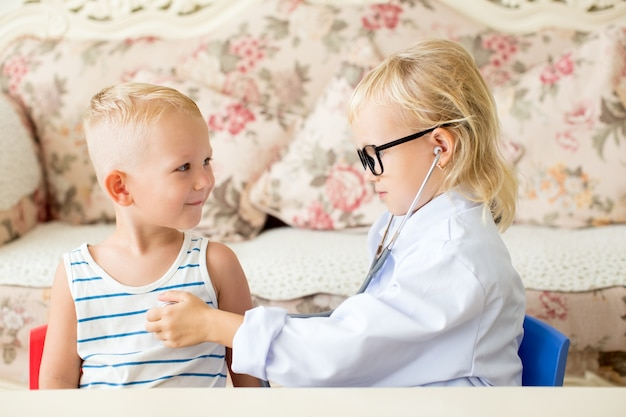 Serious little doctor examining boy patient Free Photo
