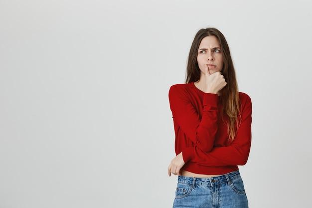 考えて、難しい選択をする深刻な外見の魅力的な女性 無料写真