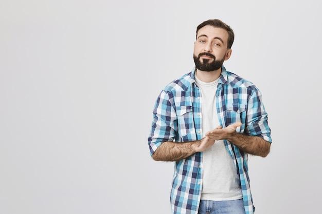 深刻に見えるひげを生やした男性が手をこすり、楽しみや収入を期待 無料写真