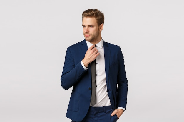 Serious-looking sassy businessman in blue classis suit, adjusting tie and looking away, holding hand in pocket, getting ready for work, waiting cab in downtown to go business meeting, greet partners Premium Photo