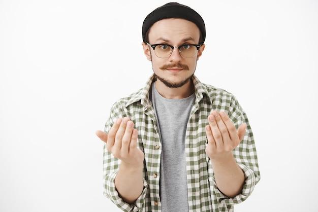Ragazzo barbuto artistico dall'aspetto serio con gli occhiali e il berretto nero che solleva i palmi vicino al corpo chiedendo di avvicinarsi a lui o di dare qualcosa che vuole tenere un oggetto nelle mani sul muro grigio Foto Gratuite