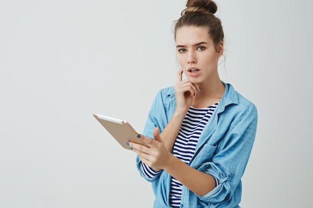 思慮深く探しているデジタルタブレットコンサルティングアシスタントを保持している真面目な女性中間作業 無料写真