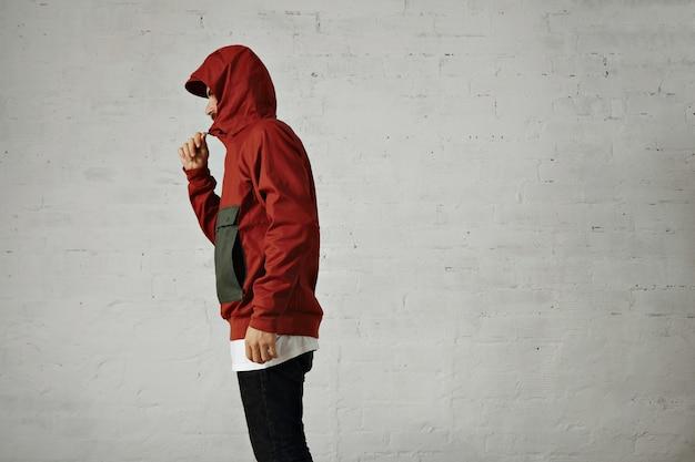 Un giovane dall'aspetto serio chiude la cerniera della sua giacca a vento rossa e grigia, ritratto dal lato isolato su bianco Foto Gratuite