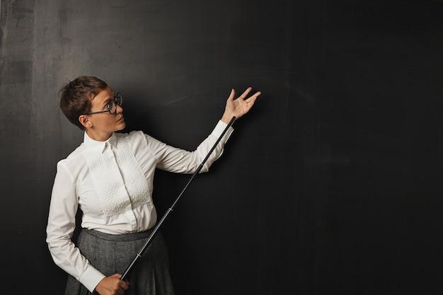 白いボタンアップブラウスとツイードスカートの真面目な若い白人女性教師は、ポインターを保持している黒い黒板に立っています 無料写真