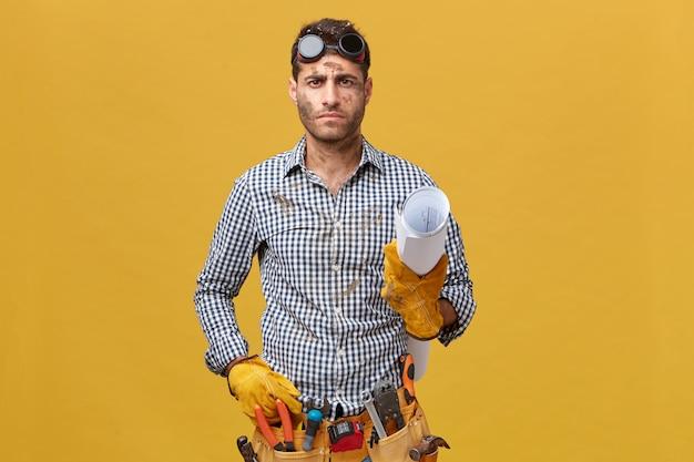 黄色の壁に分離された市松模様のシャツ、保護眼鏡、および手で紙を保持している手袋を身に着けている楽器のベルトを持つ深刻な男性ビルダー。人、修理、建設 無料写真