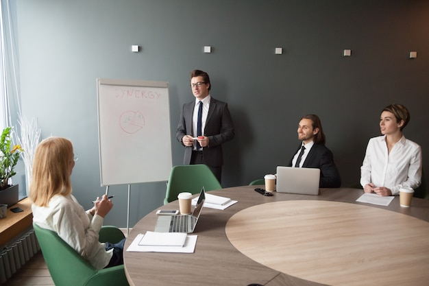 Serious male coach giving presentation on flipchart to business colleagues Free Photo
