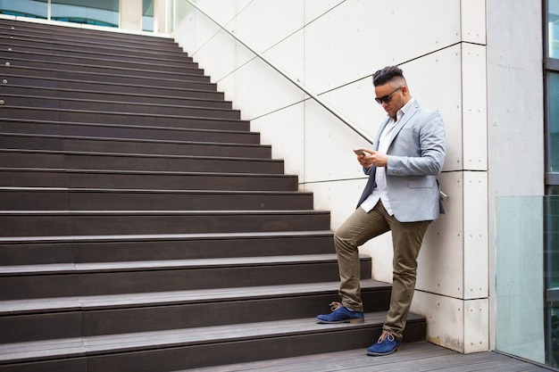 Serious male freelancer checking message on phone Free Photo