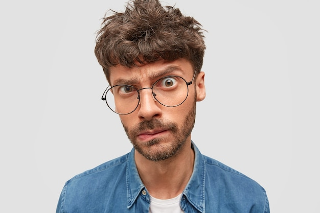 Serious man boss with trendy hairdo looks in bewilderment Free Photo
