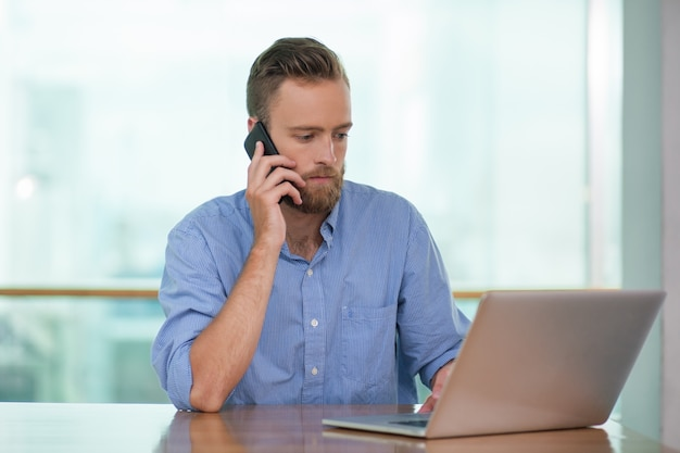 Serious Man Calling On Phone And Working On Laptop Photo