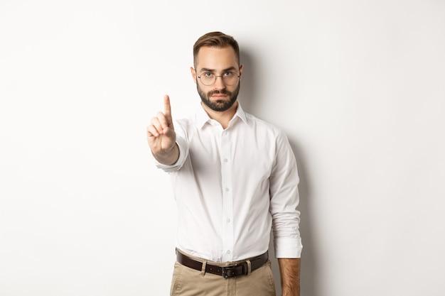 Серьезный мужчина в очках показывает знак остановки, трясет пальцем, чтобы запретить и запрещать, стоит белым Бесплатные Фотографии
