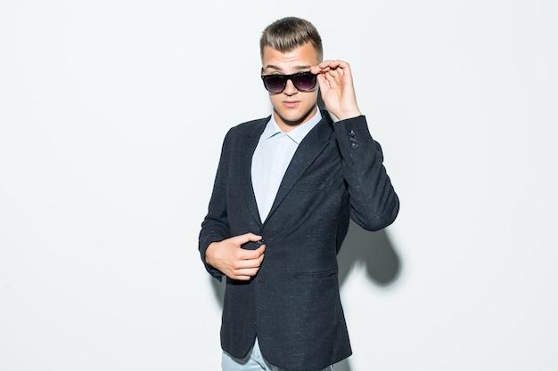 Серьезный мужчина в люксе позирует в современных солнцезащитных очках перед светлой стеной Бесплатные Фотографии
