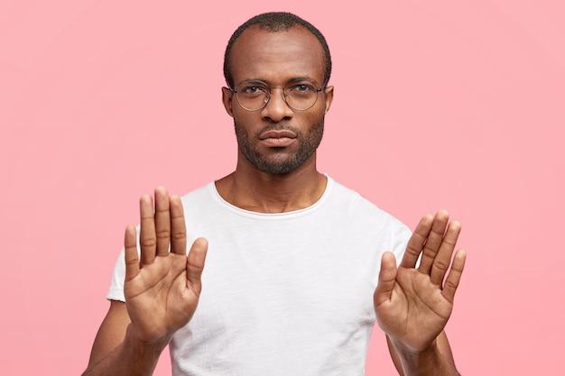 Серьезный мужчина делает стоп-жест, что-то отвергает, стоит в помещении у розовой стены Бесплатные Фотографии
