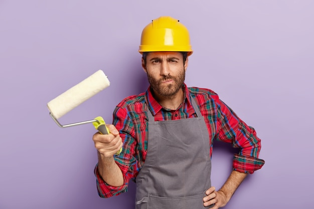 Serious man painter holds painting roller, does redecoration at home, paints walls, wears protective helmet and apron, poses indoor, busy with repairing and renovation, isolated on purple wall. Free Photo