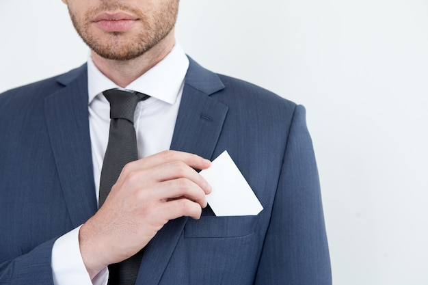 Serious man putting business card into pocket Free Photo
