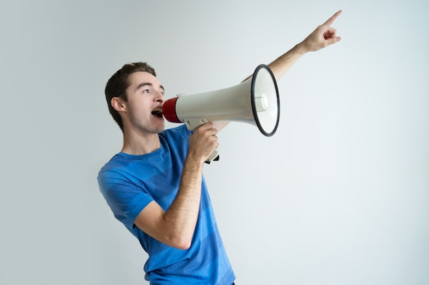 Serious man shouting into megaphone and pointing away Free Photo
