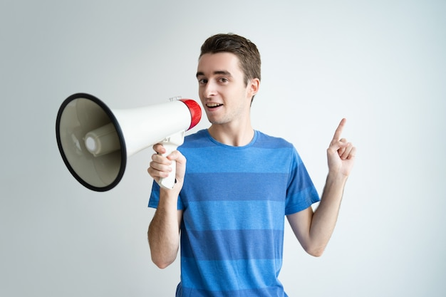 Serious man speaking into megaphone and pointing upwards Free Photo