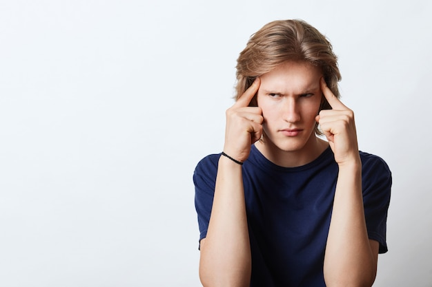 Serious man trying to concentrate, keeping fingers on head, making important decison looking with angry expression. young businessman being busy with work trying to focus on something important Free Photo