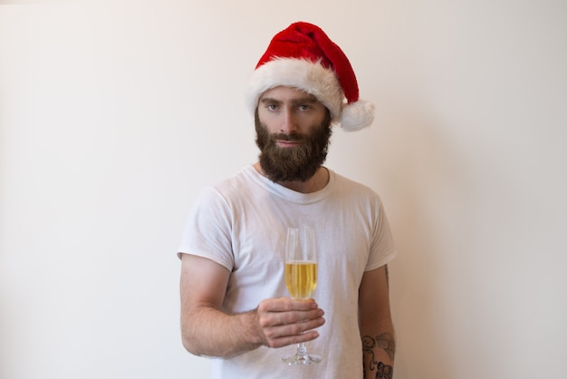 Serious man wearing santa hat and holding goblet with champagne Free Photo