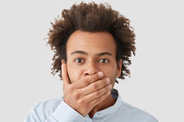 アフロヘアカットの真面目な男、手のひらで口を覆い、言葉を失い、情報を陰謀に保つ 無料写真
