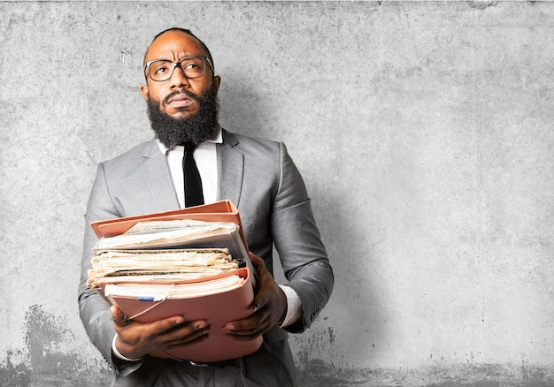 Serious man with lots of papers and folders Free Photo