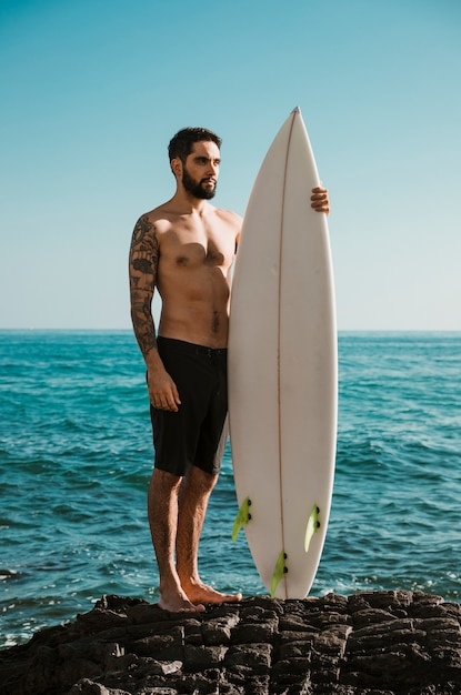 Serious man with surfboard standing on rock Free Photo