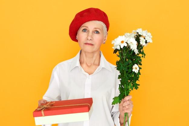 데이지의 무리와 생일 선물을 만드는 과자 상자를 들고 빨간 모자에 고립 된 짧은 머리 포즈와 심각한 성숙한 유럽 여자. 당신에게 꽃을주는 세련된 중년 여성 무료 사진