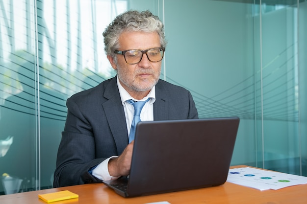 Serious mature executive wearing suit and glasses, working at computer in office, using laptop at table Free Photo