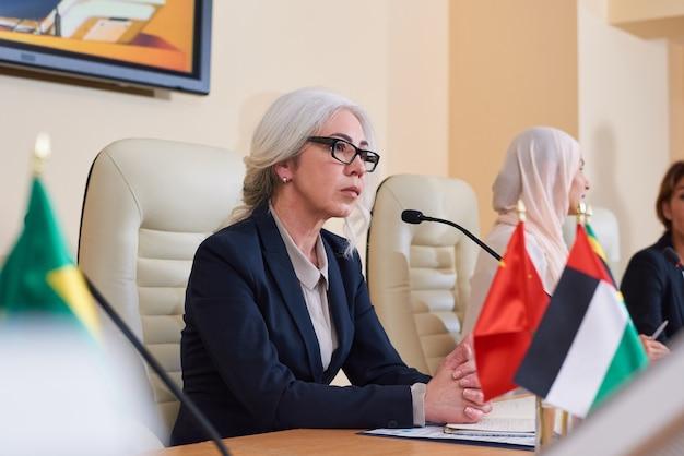 エレガントなスーツを着た深刻な成熟した女性代表者が会議でそれらに答える前に聴衆の質問に耳を傾けます Premium写真
