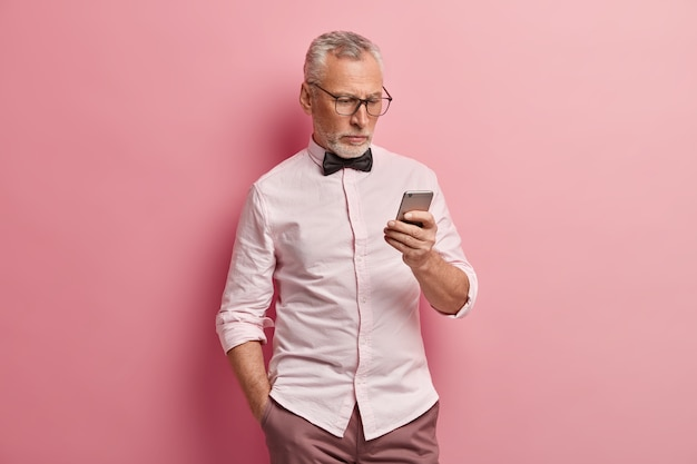 L'uomo maturo serio utilizza lo smartphone, legge le notizie online, tiene la mano in tasca, essendo sempre in contatto, isolato su sfondo rosa. Foto Gratuite