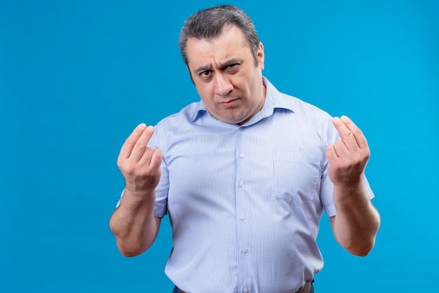 Serious middle age man in blue striped shirt gesturing with hands try to explain his point of view on a blue background Free Photo