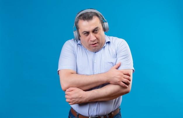 ヘッドフォンで青い縦縞のシャツを着ている深刻な中年男が青い背景に暖かく滞在しようとして冷たく感じ 無料写真