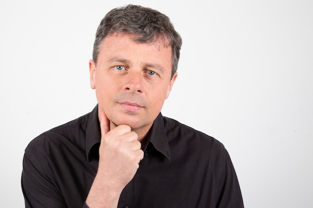 Serious middle-aged man with hand on chin Premium Photo