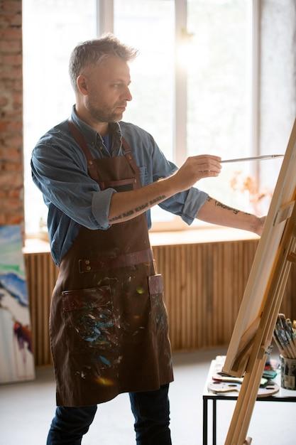 彼のワークショップやスタジオで絵画しながらイーゼルの絵を見て絵筆を持つ深刻な中年男 Premium写真