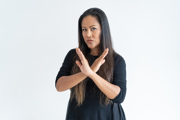 Serious middle-aged woman showing crossed hands Free Photo