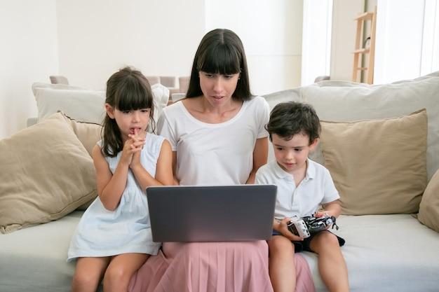 深刻なママとリビングルームのラップトップで映画を見て2人の心配している子供。 無料写真