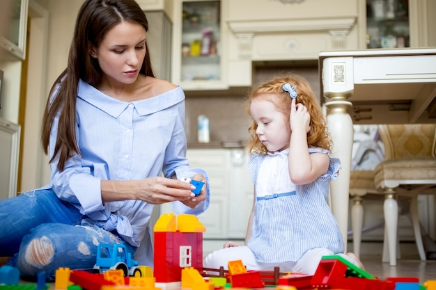 Serious mother or nanny playing with little girl Premium Photo