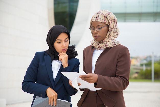Serious muslim business colleagues reviewing documents outside Free Photo