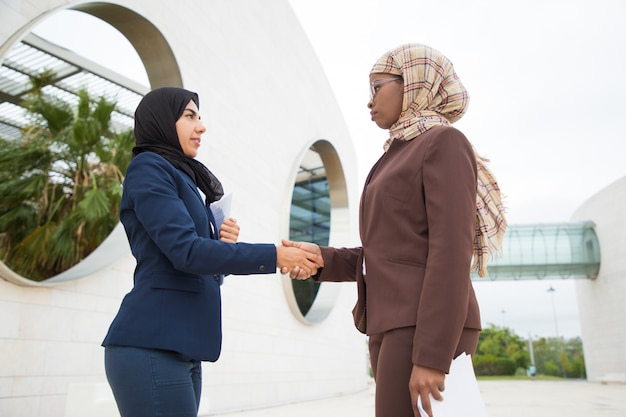 Serious muslim businesswomen greeting each other Free Photo